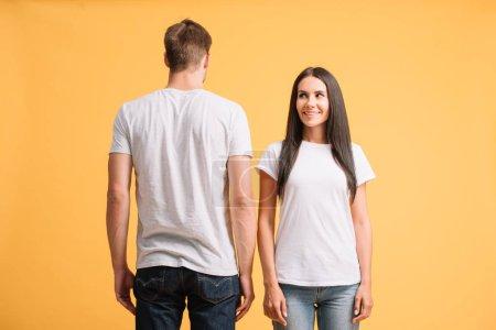 Photo pour Beau couple souriant posant en t-shirts blancs, isolé sur jaune - image libre de droit