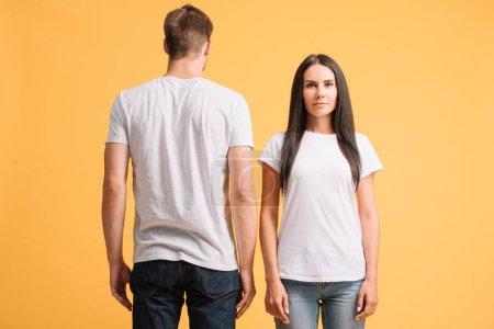 Photo pour Beau couple posant en t-shirts blancs, isolé sur jaune - image libre de droit