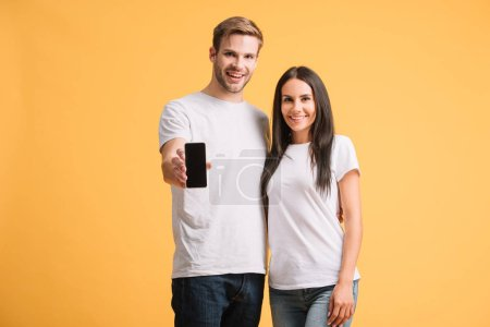 Photo for Smiling couple showing smartphone with blank screen isolated on yellow - Royalty Free Image