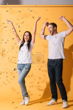 Photo for Happy couple have fun on yellow with golden confetti - Royalty Free Image
