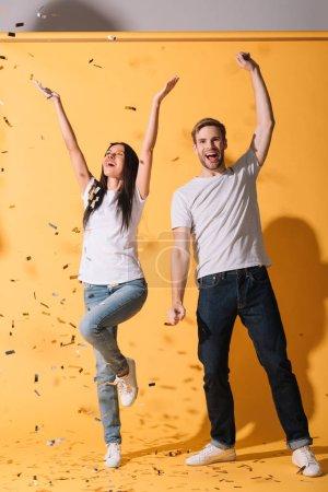 Photo pour Danse excitée de couples sur le jaune avec des confettis d'or - image libre de droit