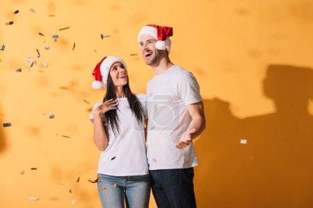 Photo pour Couples heureux dans des chapeaux de santa étreignant sur le jaune avec des confettis dorés - image libre de droit