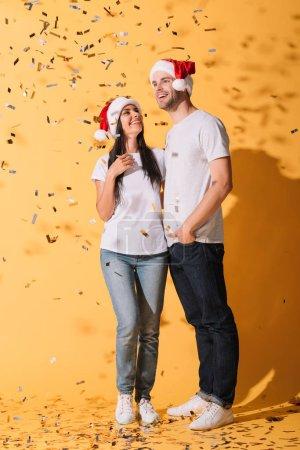 Foto de Novio y novia en santa sombreros abrazando en amarillo con confeti dorado - Imagen libre de derechos