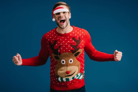 Photo for Excited man shouting and posing in christmas sweater and eyeglasses with santa hat, isolated on blue - Royalty Free Image