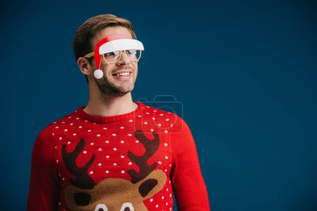 Photo for Smiling man posing in christmas sweater and eyeglasses with santa hat, isolated on blue - Royalty Free Image
