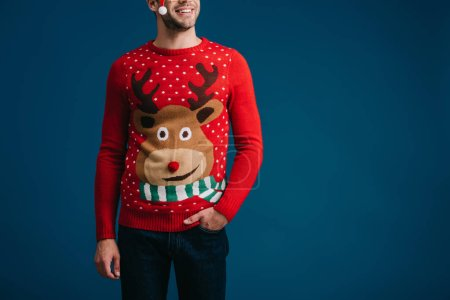 handsome man posing in christmas sweater and eyeglasses with santa hat, isolated on blue