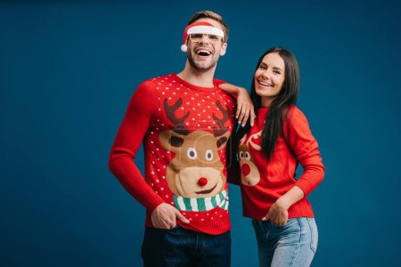 Photo for Boyfriend in glasses with santa hat hugging cheerful girlfriend isolated on blue - Royalty Free Image