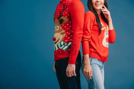 cropped view of couple in christmas sweaters standing back to back isolated on blue