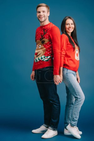 happy couple in christmas sweaters holding hands isolated on blue