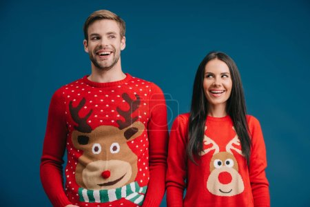 Photo for Excited couple posing in christmas sweaters isolated on blue - Royalty Free Image