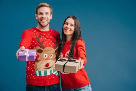 Photo pour Couple souriant en chandails rouges tenant cadeaux de Noël isolé sur bleu - image libre de droit