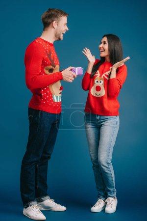 novio guapo presentando regalo de Navidad a novia sorprendida aislada en azul