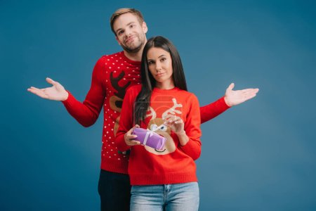 girlfriend holding christmas present, boyfriend standing behind with shrug gesture isolated on blue