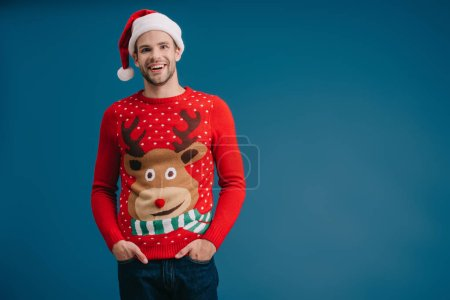 smiling man posing in santa hat and christmas sweater isolated on blue