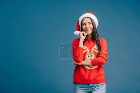 Photo for Smiling woman posing in santa hat and christmas sweater isolated on blue - Royalty Free Image