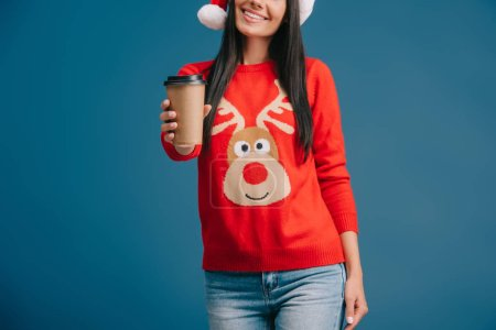 Photo for Cropped view of smiling girl in santa hat and christmas sweater holding coffee to go, isolated on blue - Royalty Free Image