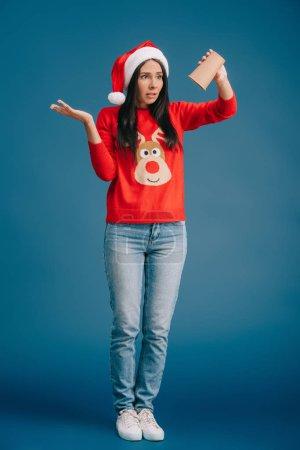 Photo pour Bouleversé fille dans santa chapeau et chandail de Noël tenant tasse vide de café, isolé sur bleu - image libre de droit