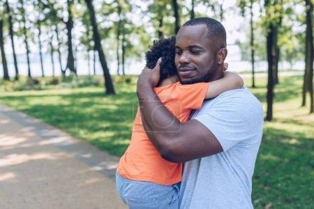 Photo pour Heureux père afro-américain tenant et embrassant adorable fils dans le parc - image libre de droit