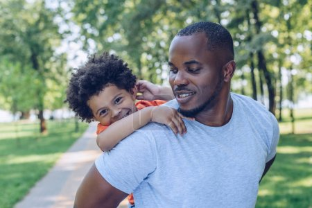 Photo pour Handsome african american man piggybacking cheerful son in park - image libre de droit