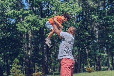 Photo pour Jeune Africain américain tenant son fils joyeux au-dessus de la tête tout en s'amusant dans le parc - image libre de droit
