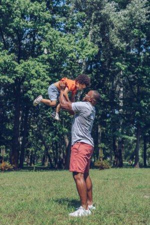 Photo pour Gentil Américain d'origine africaine tenant son fils joyeux au-dessus de la tête tout en s'amusant dans le parc - image libre de droit