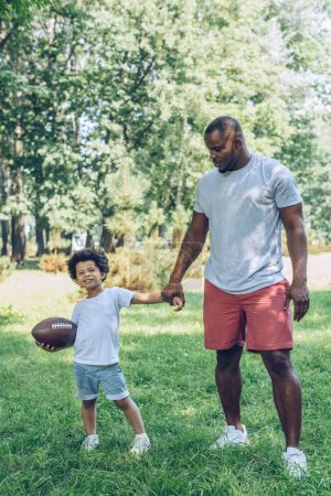 Photo for Cute african american boy hoding rugby ball while holding hands with father in park - Royalty Free Image