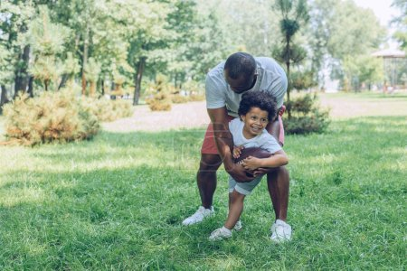 Photo for Cheerful african american boy playing rugby with father in park - Royalty Free Image