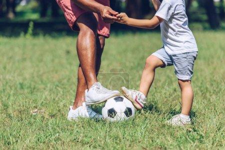 Photo pour Crochet vue d'un père et d'un fils africains américains jouant au football dans le parc - image libre de droit