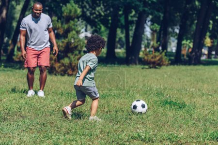 Photo for Young african american father playing football with cute son in park - Royalty Free Image