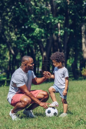Photo pour Handsome african american man teaching son playing football in park - image libre de droit