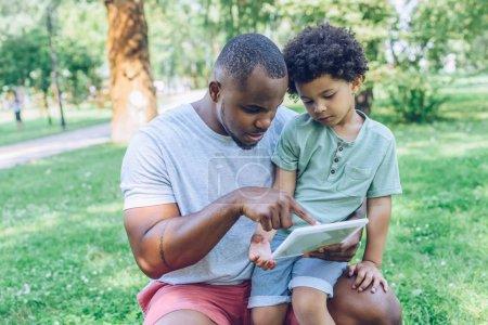 Photo pour Jeune père afro-américain en utilisant une tablette numérique pour adorable fils dans le parc - image libre de droit