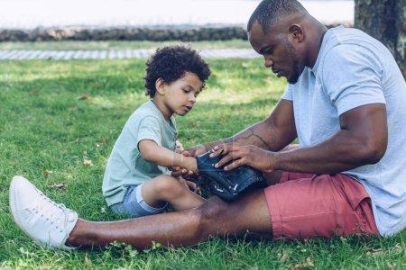 Photo pour Bel homme afro-américain montrant gant de baseball à son fils assis sur la pelouse dans le parc - image libre de droit