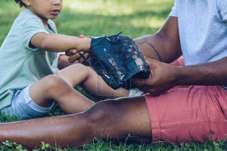 Photo pour Vue recadrée d'un homme afro-américain montrant un gant de baseball à son fils assis sur une pelouse dans un parc - image libre de droit
