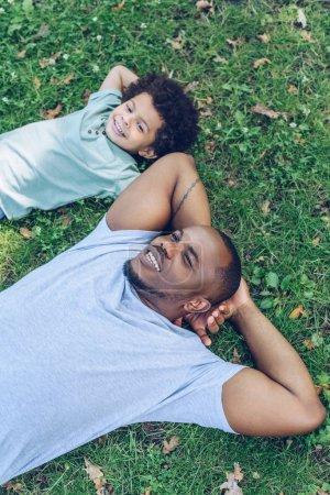 Foto de Feliz padre e hijo africoamericano acostados sobre el césped mientras descansan en el parque. - Imagen libre de derechos