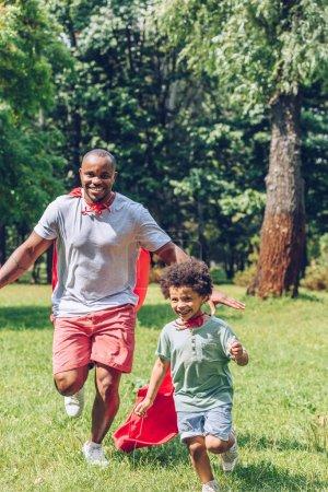 Photo pour Un père et un fils africains joyeux courent en costumes de super-héros dans le parc - image libre de droit