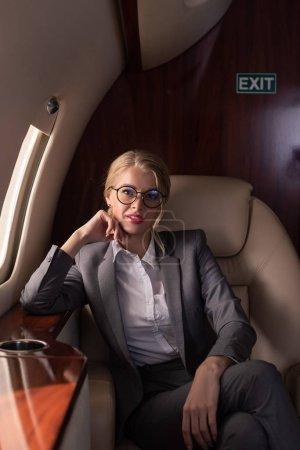 Schöne Geschäftsfrau sitzt während Geschäftsreise im Flugzeug