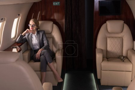 Photo for Beautiful blonde businesswoman sitting in plane during business trip - Royalty Free Image