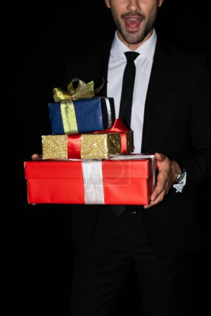 Photo for Cropped view of excited man holding gift boxes, isolated on black - Royalty Free Image