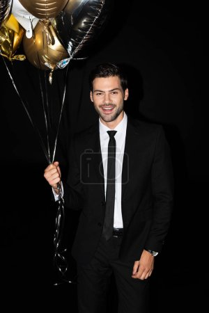 Photo for Stylish cheerful man holding golden balloons, isolated on black - Royalty Free Image