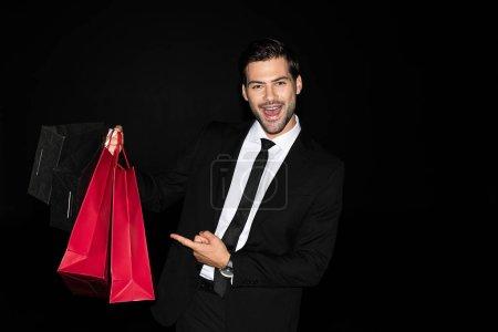 fröhlich eleganter Mann im Anzug zeigt auf Einkaufstüten auf schwarz