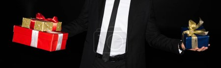 cropped view of stylish man holding gift boxes, isolated on black