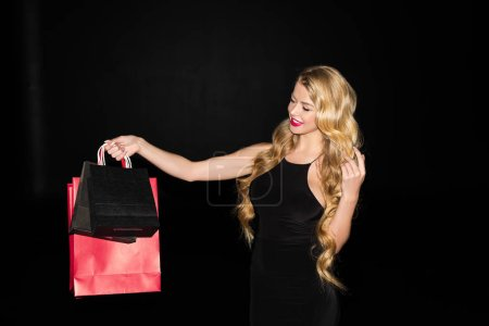 Photo for Beautiful smiling woman holding shopping bags, isolated on black - Royalty Free Image