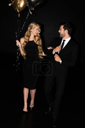 Photo for Beautiful cheerful couple with golden balloons on party isolated on black - Royalty Free Image