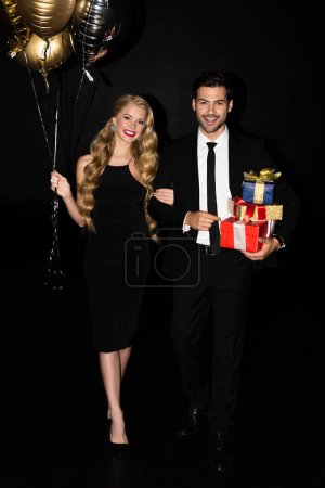 Photo for Cheerful couple with golden balloons and presents isolated on black - Royalty Free Image
