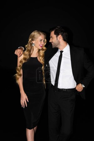 Photo for Smiling man hugging attractive girlfriend isolated on black - Royalty Free Image