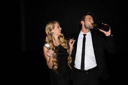 Photo pour Beau couple heureux buvant du champagne lors d'une fête isolée sur noir - image libre de droit