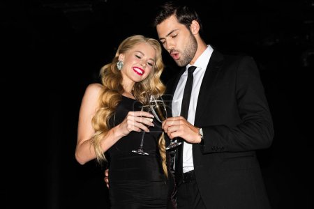 Photo pour Beautiful couple clinking with glasses on champagne isolated on black - image libre de droit