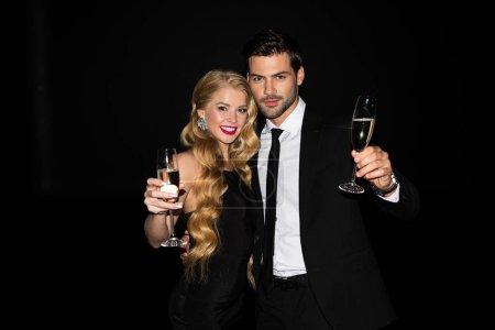 Photo pour Beau couple heureux célébrant avec champagne isolé sur noir - image libre de droit