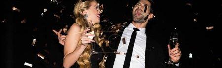 Photo pour Couple excité célébrant avec champagne sur noir avec confettis dorés - image libre de droit