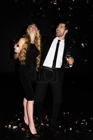 Foto de Excited young couple celebrating with champagne on black with golden confetti - Imagen libre de derechos